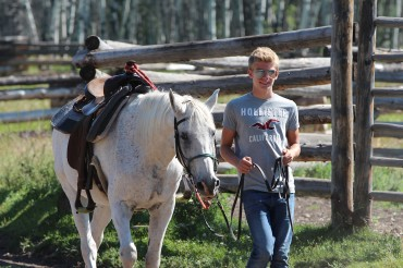 A guest and his horse prepare together for a ride at Siwash Lake Wilderness Resort