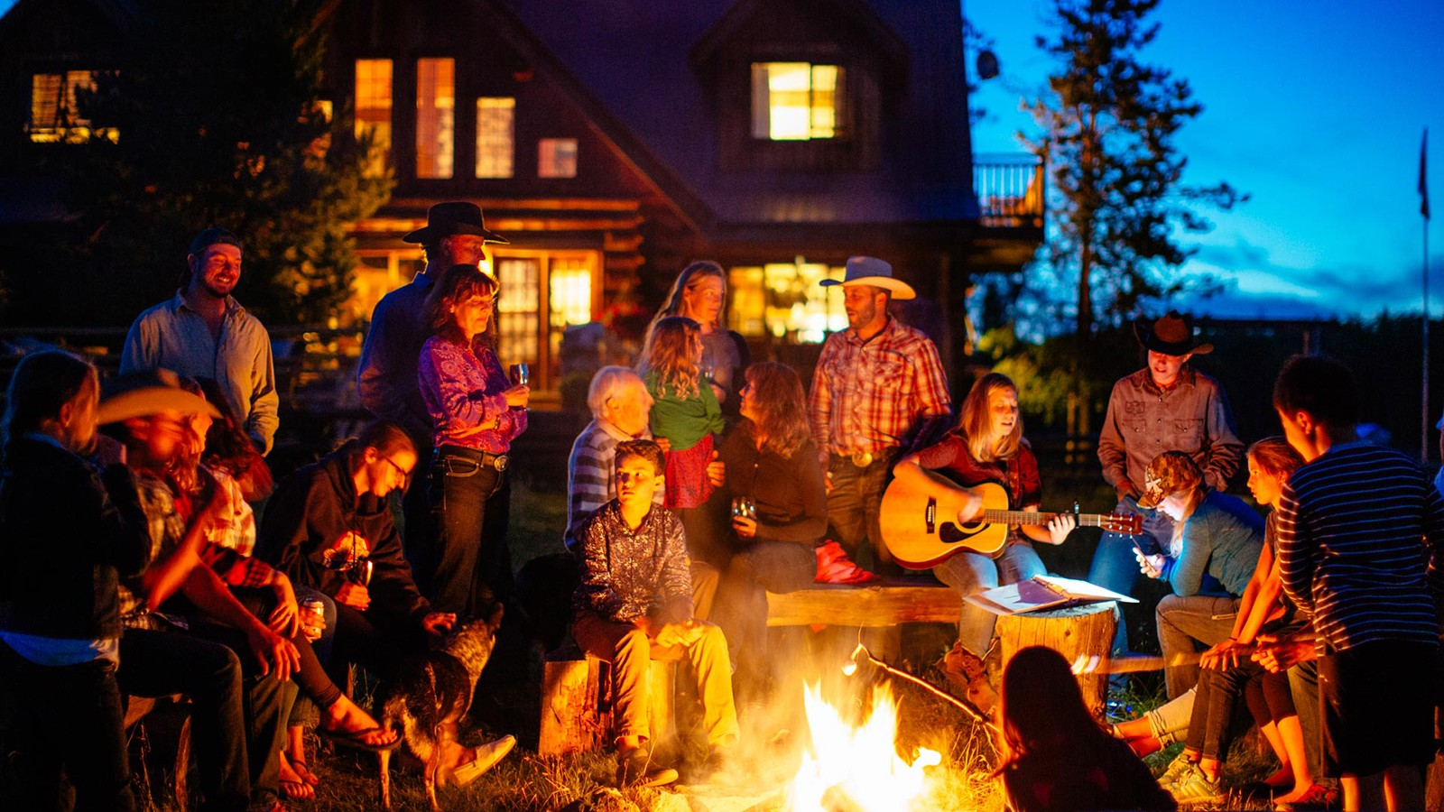 Connecting with loved ones by the campfire in front of the main lodge at Siwash Lake Wilderness Resort